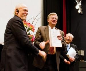 ILC TDR 完成発表会において、バリー・バリッシュ氏(GDE ディレクター:写真左)と山田作衛氏(RD ディレクター:写真右)がジョナサン・バガー氏(ILCSC 議長:写真中央)にTDR のドラフトを提出した。